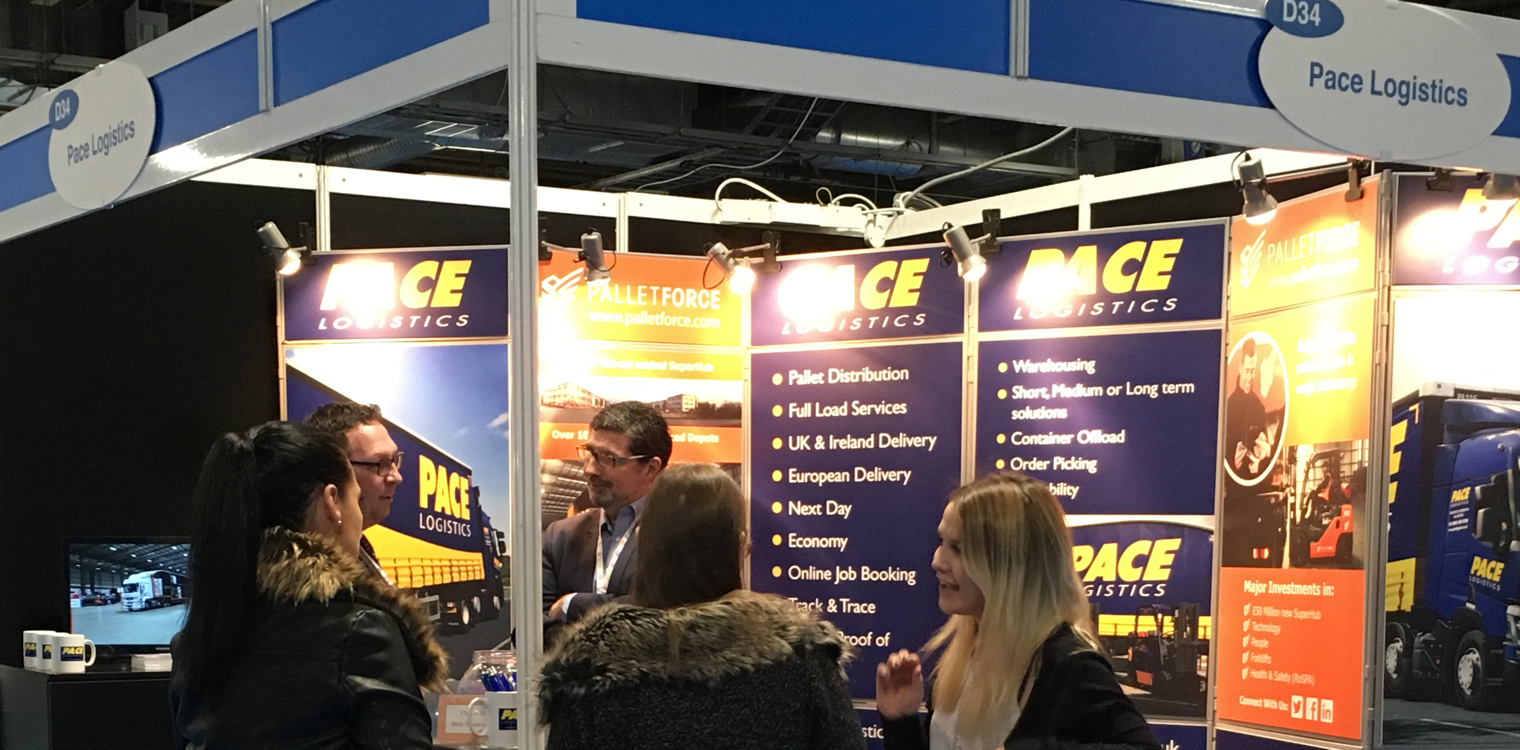 Visitors discussing logistics and pallet delivery at Manchester exhibition
